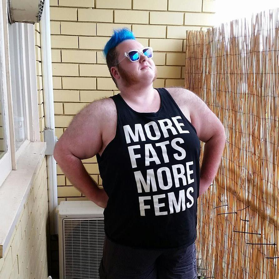 Erin wearing a t-shirt that reads 'more fats more fems'