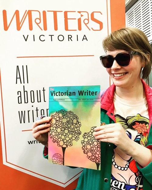 Alex standing in front of a poster for Writers Victoria and holding a copy of The Victorian Writer publication